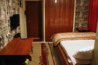 Номер оборудован большой кроватью, столом и тумбочками.